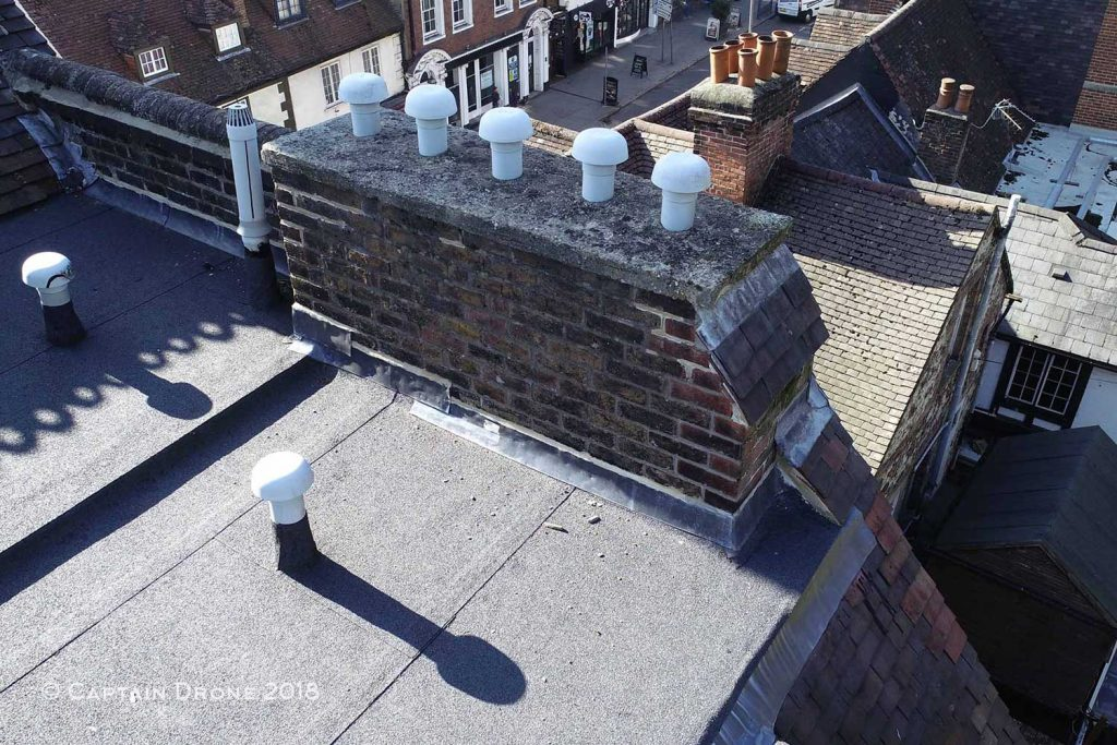 Debris from concrete crumbling on flat roof - Captain Drone roof inspection service